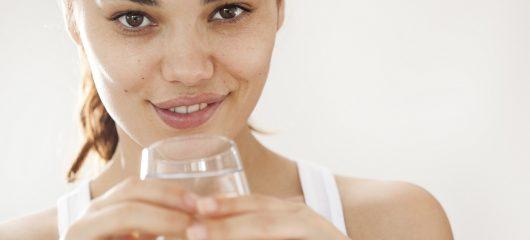 kobieta ze szklanką wody zapobiega odwodnieniu